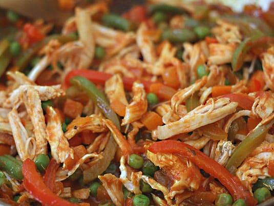 Incorporar el pollo precocido, revolver bien de manera que todos los ingredientes queden bien mezclados para añadirlos al arroz.