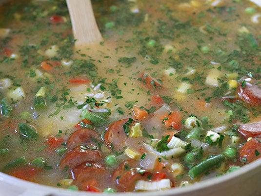 Se adicionan el agua o caldo, los vegetales mixtos, el apio, el perejil y las salchichas.